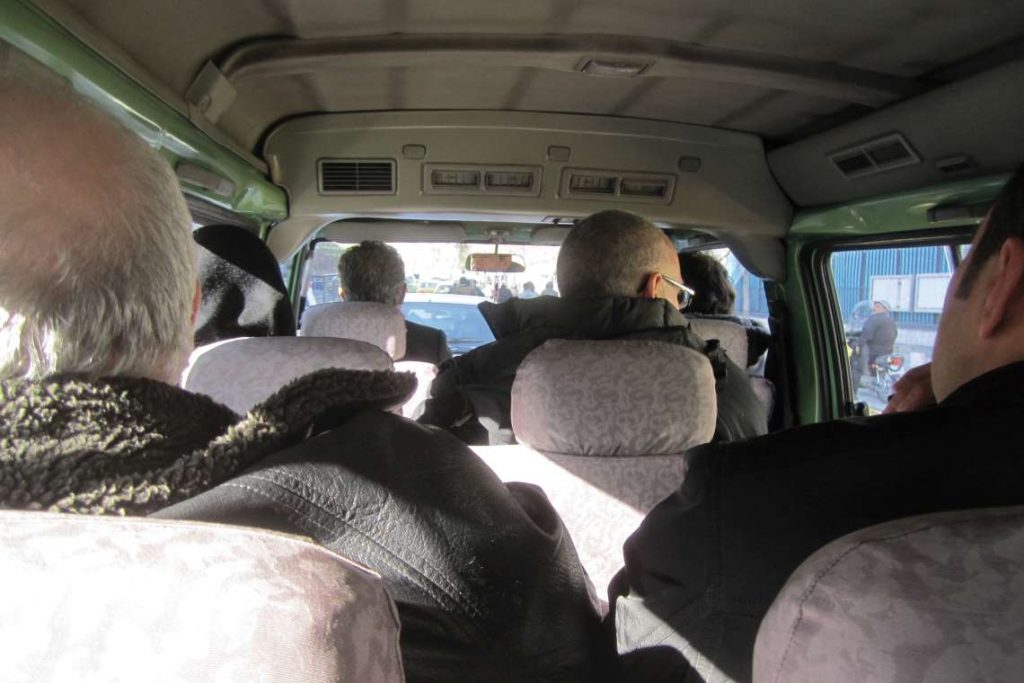 The theater jury in their minivan going through an anti-government demonstration.