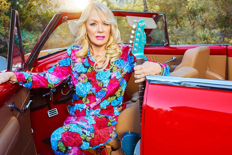 Press photo of Nancy Wilson of Heart sitting in a convertible with a guitar