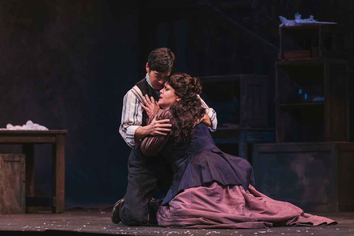 Two opera singers embrace each other while kneeling in 19th century costumes.